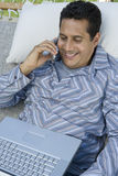 Relaxed Man On Hammock Using Cell Phone Royalty Free Stock Images