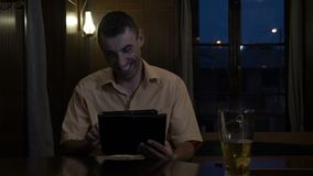 Relaxed man having a beer and laughing and chatting on social media at bar - stock video