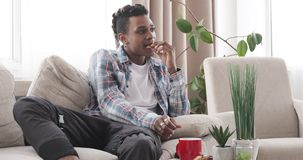 Relaxed man having breakfast while watching tv in living room. Relaxed african american man having breakfast while watching tv in the living room stock video