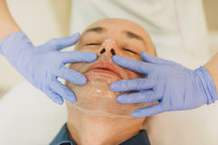 Relaxed man having a face massage and a peeling treatment Stock Photography