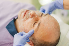 Relaxed man having a face massage and a peeling treatment Royalty Free Stock Photos