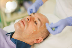 Relaxed man having a face massage and a peeling treatment Royalty Free Stock Image
