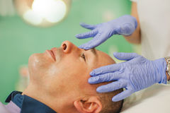 Relaxed man having a face massage and a peeling treatment Stock Photo
