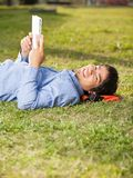 Relaxed Man Holding Book While Lying On Grass At. Side view portrait of relaxed young man holding book while lying on grass at college campus Stock Images