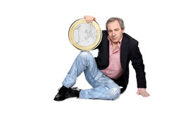 Relaxed man holding an euro coin. Relaxed mature man holding a big euro coin isolated on white Stock Photography