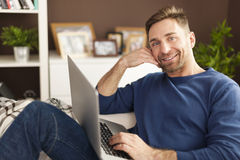Relaxed man at home. Portrait of smiling man with laptop on sofa Royalty Free Stock Photo
