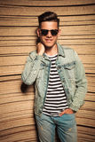 Relaxed man in jeans jacket and sunglasses poses Royalty Free Stock Images