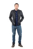 Relaxed man in jeans and leather jacket smiling at camera with hands in pockets. Full body length portrait isolated over white studio background Stock Photo