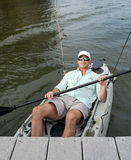 Relaxed Man Kicks Back in Fishing Kayak Royalty Free Stock Image