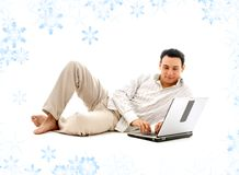 Relaxed man with laptop. Computer and snowflakes Royalty Free Stock Images