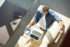 Relaxed man with laptop. Top view shot of casual man with laptop relaxing in his cosy modern home Stock Images