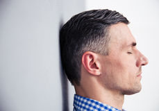 Relaxed man leaning on the wall. Side view portrait of a relaxed man leaning on the wall Royalty Free Stock Photography