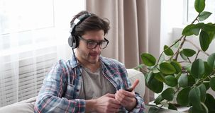 Man listening music using headphones and mobile phone in living room stock footage
