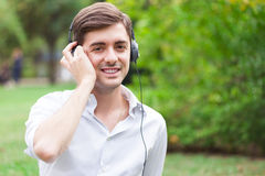 Relaxed man listening to music. Man enjoying good music at the park Royalty Free Stock Image