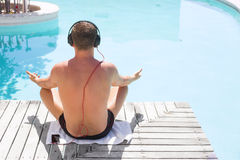 Relaxed man listening to music on headphones by the swimming pool Stock Image