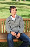 Relaxed man listening to some music. In the park Stock Photo