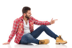 Relaxed man in lumberjack shirt pointing Stock Photo
