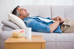 Relaxed man lying on the couch Stock Photography