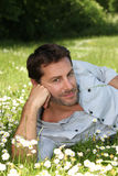 Relaxed man lying in a field Royalty Free Stock Images
