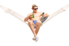 Relaxed man lying in a hammock and holding a beer Royalty Free Stock Images