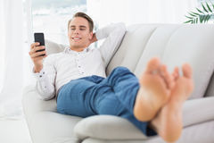 Relaxed man lying on sofa and text messaging Stock Image