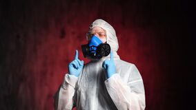 Relaxed man-medic wearing protective suit, goggles and a respirator dances.