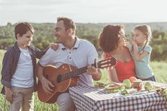 Relaxed man playing guitar for family on picnic. Joyful father and son are singing favorite song to guitar. Woman is playing with daughter and smiling. They are stock photos
