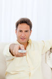 Relaxed man pointing a remote to the camera Stock Photography
