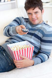 Relaxed man with popcorn showing the remote Royalty Free Stock Photography