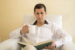 Relaxed man reading a book Stock Photos
