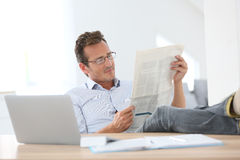 Relaxed man reading newspaper at home Stock Image