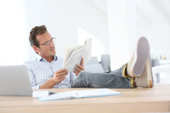 Relaxed man reading newspaper at office Royalty Free Stock Images