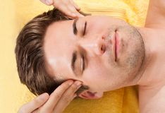Relaxed man receiving forehead massage in spa Royalty Free Stock Photos