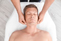 Relaxed man receiving head massage. In wellness center, top view stock image