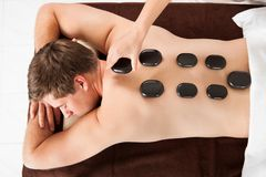 Relaxed man receiving hot stone therapy in spa Royalty Free Stock Photography