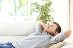 Relaxed man resting on a couch at home. Relaxed man resting lying on a couch with the hands on the head at home Stock Photography