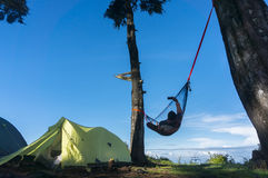 Relaxed man selfie and lying in a comfortable hammock. During camping with blue sky Royalty Free Stock Image