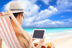 Relaxed man sitting on beach chairs and touching tablet. With beach and sky Royalty Free Stock Images