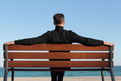 Relaxed man sitting on a bench Stock Photography