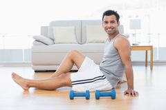 Relaxed man sitting on floor with dumbbells in the living room. Side view portrait of a smiling relaxed young man sitting on floor with dumbbells in the living Stock Photography