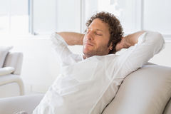 Relaxed man sitting with hands behind head at home Royalty Free Stock Photos