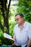 Relaxed man sitting in park and reading Royalty Free Stock Photos