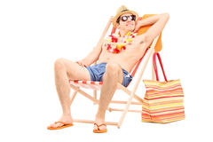 Relaxed man sitting shirtless in a sun lounger Royalty Free Stock Image