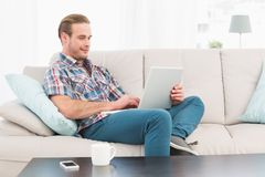 Relaxed man sitting on sofa using laptop. At home in the living room Stock Photo