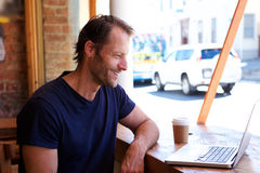 Relaxed man smiling with laptop at cafe Stock Photos