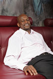 Relaxed man on sofa. Relaxed middle aged african man sitting on red leather sofa Royalty Free Stock Photo