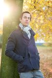 Relaxed man standing outdoors in park on Autumn day Stock Photos