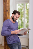 Relaxed man standing reading a newspaper Stock Photos