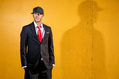 Relaxed man in suit by wall. A young man in a suit with a red tie and hat standing in front of a yellow wall Stock Photo