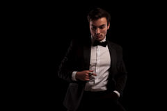 Relaxed man in tuxedo and bowtie looking down Stock Photography